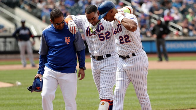 Mets' Yoenis Cespedes (52) is helped off the field by first base coach Tom Goodwin (22) and a trainer during the fourth inning against the Atlanta Braves  on Thursday.