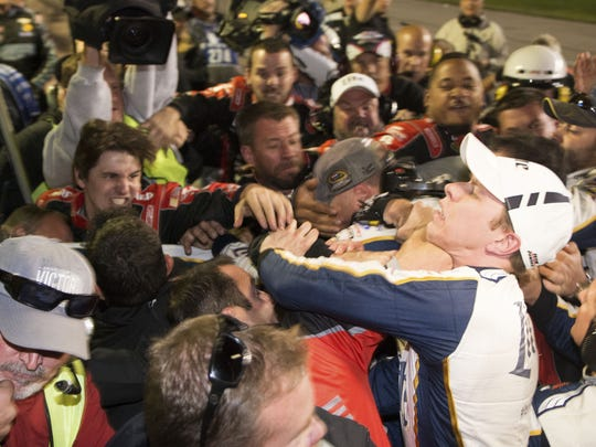 Brad Keselowski, right, is punched during a fight after the NASCAR Sprint Cup Series auto race at Texas Motor Speedway in Fort Worth, Texas, Sunday, Nov. 2, 2014.  The crews of Jeff Gordon and Keselowski fought after the race.
