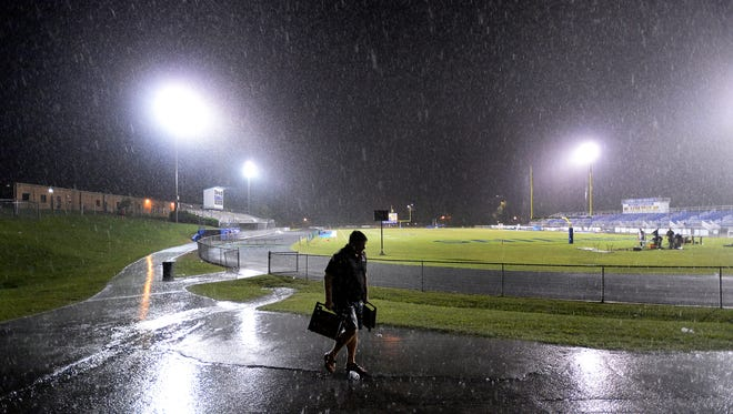A man leaves the Brentwood High School football stadium after the game between Ravenwood and Brentwood was called due to lightning on Friday, Aug. 26, 2016, in Brentwood, Tenn.
