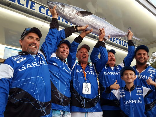 Jason Phillips (left), Ryan Rowe, team captain Steve Sprague, James Gilchrist, Billy Broadbeck and Christopher Sprague (front row), celebrate Team Tuppen's/Garmin Marine's Southern Kingfish Association Mercury Tournament Trail National Championship in the open class Saturday by hoisting the 62.33-pound kingfish the team caught Friday. The team caught a 37 Saturday to win with 99 aggregate pounds for two kingfish.
