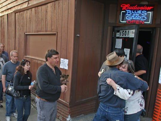 Lynette Webster, right, hugs regular costumers as she works the door for the $10 cover charge at The Last Bash held at Blues on Grand on Oct. 23, 2010. Webster had worked at the bar since its beginning.