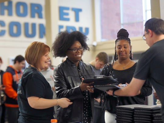 Ivory Jackson, a junior at Hillcrest High School, laughs as she receives a laptop from David Burks, an IT employee with the school district, and Nicole Lemmon, Ignite assistant director of blended learning development.