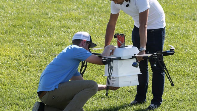 Workers load a package of simulated blood and other medical samples to be carried in a drone for a ship-to-shore delivery simulation Wednesday in Lower Township.