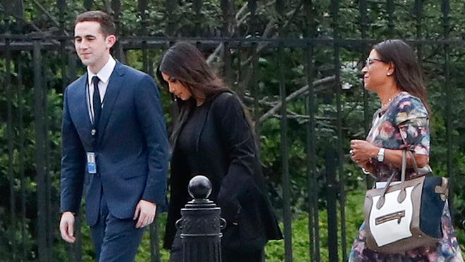 Kim Kardashian, center, arrives with her attorney Shawn Chapman Holley at the security entrance of the White House in Washington on Wednesday.