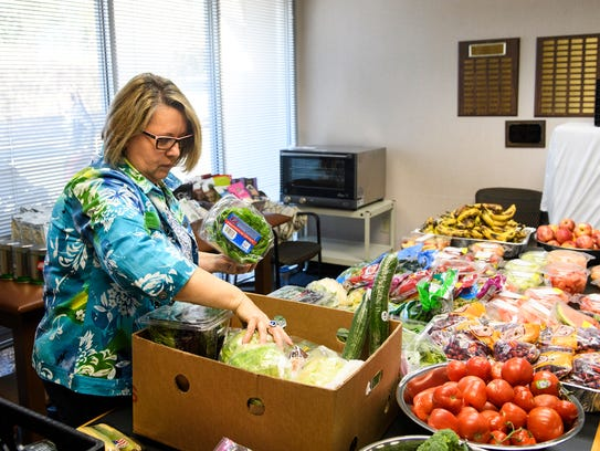 Volunteer Delores Eanes organizes produce for the free