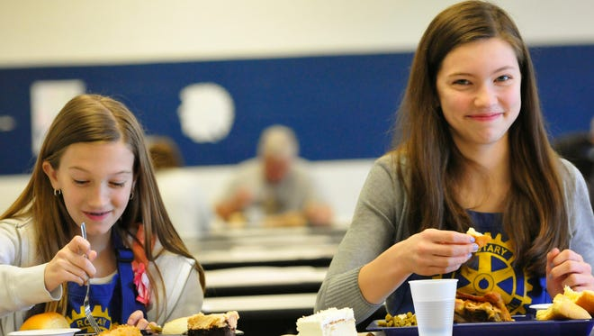 Bella Shupp, 11, left, and her sister Madi, 13, eat lunch during the annual Chicken 'n Stuff, Monday April 6, 2015.
