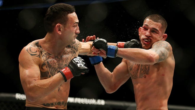 Anthony Pettis (right) absorbs a blow from Max Holloway in their UFC fight Saturday night.