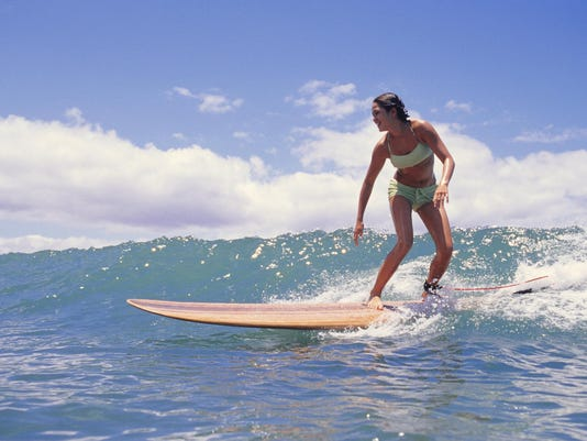 Woman surfing on ocean wave