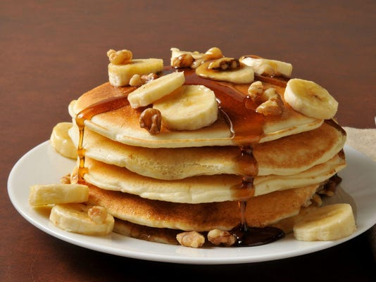 Pile of pancakes with banana and maple syrup on its top