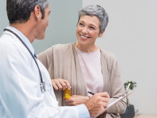 Doctor writing on pad while talking to smiling older woman with short gray hair
