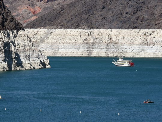 Boats travel in front of mineral-stained rocks on the upstream side of the Hoover Dam. Lake Mead is at historically low levels.