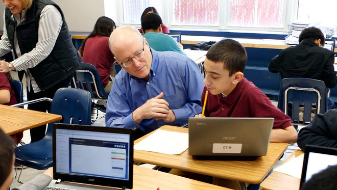 Yonkers Partners in Education board member Bud Kroll works with Brandon Couto, 13, in an eighth-grade math class at Palisade Preparatory School on Dec. 12 in Yonkers.