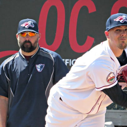 Mickey Storey (right), warms up before Thursday's game under the watchful eye of pitching coach Cory Domel (left).