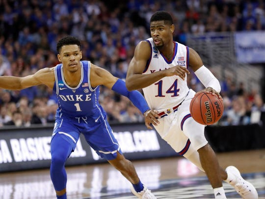 Kansas' Malik Newman (14) heads to the basket around Duke's Trevon Duval (1) during the first half of a regional final game in the NCAA men's college basketball tournament Sunday, March 25, 2018, in Omaha, Neb. (AP Photo/Nati Harnik)