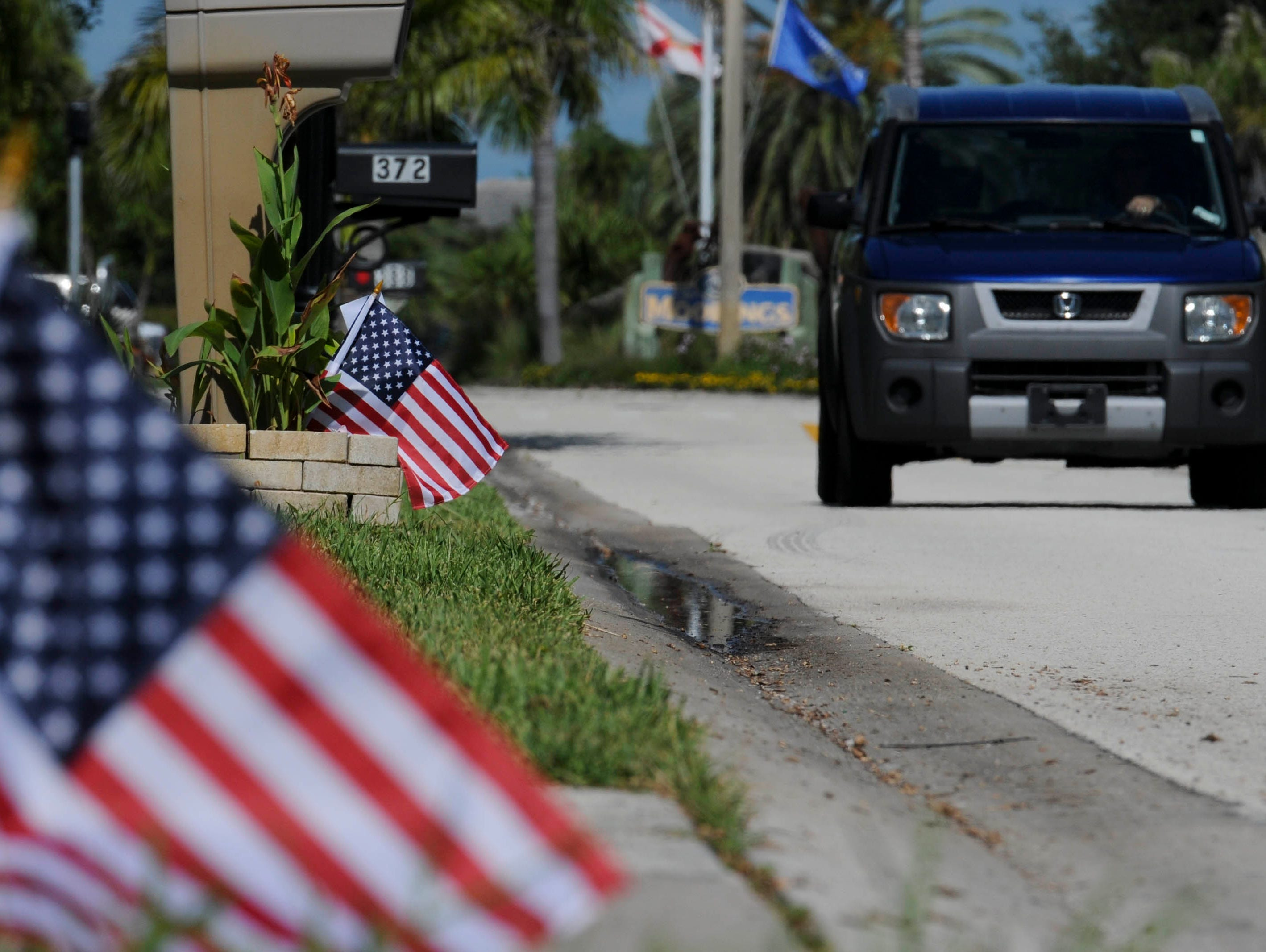 American flags line the streets so Satellite Beach Thursday morning. Students from Satellite High's football and ROTC squads help distribute American flags to town residents as part of a fundraiser for the school.