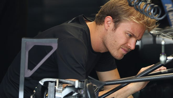 Nico Rosberg inspects a part on his car in the garage during previews for the Malaysia Formula One Grand Prix at Sepang Circuit on Friday.