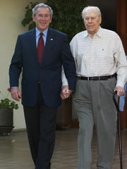 President George W. Bush (L) walks with former president Gerald Ford from Ford's residence after a courtesy call by Bush on April 23 2006 in Rancho Mirage.