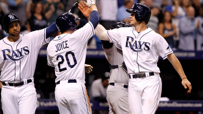 Tampa Bay Rays right fielder Wil Myers (9) is congratulated by right fielder Matt Joyce (20) and first baseman James Loney (21) after he hit a 3-run home run against the New York Yankees during the fifth inning at Tropicana Field.