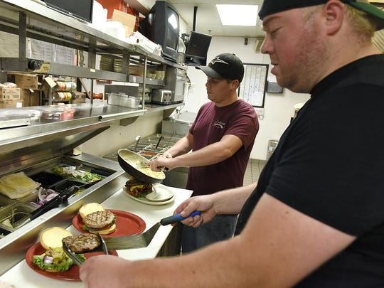 Cooks Andrew Yunker and Travis Basol create burgers during lunch at G-Allen's Restaurant & Sports Bar on Aug. 20 in Sartell.