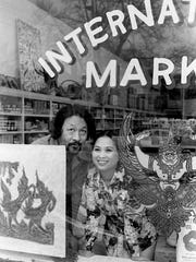 Owners Win and Patti Myint look out the window of International Market on Belmont Boulevard, on Feb. 16, 1976.