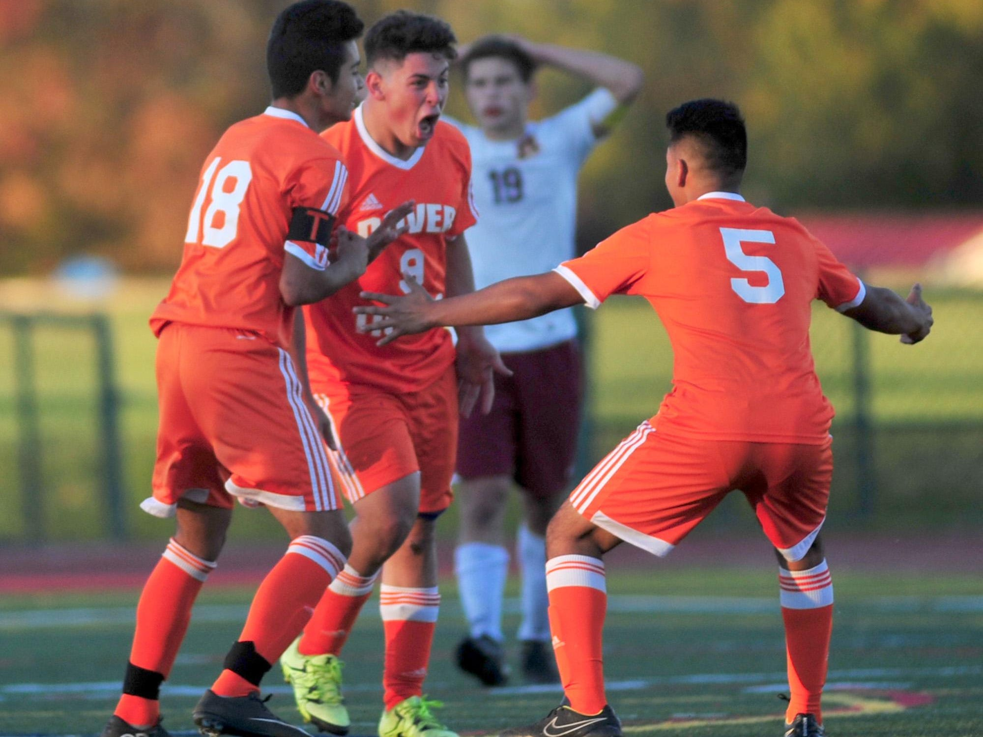 Seniors Leandro Suarez and Armando Caamano celebrate Dover's tying goal with sophomore Isaiah Flores, who scored.