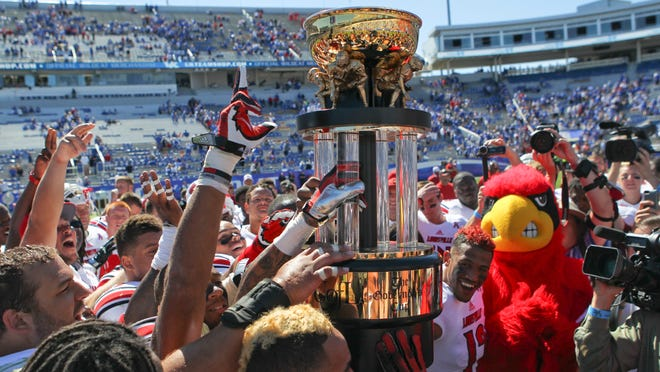 Louisville players celebrate with the Governor's Cup after the Cardinals beat Kentucky 27-13 last season at Commonwealth Stadium.