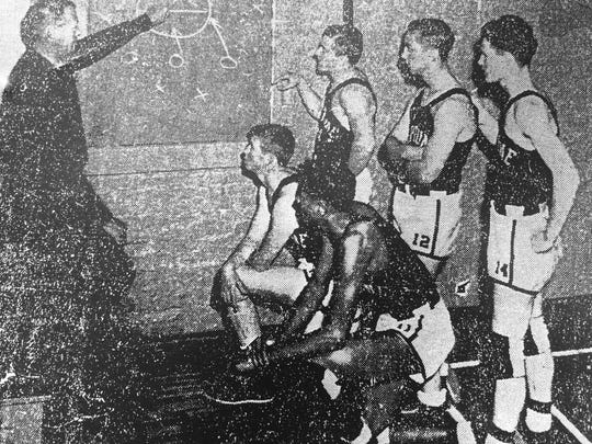 The Neptune starting five from the 1941-42 season listen to coach Ken Townsend.