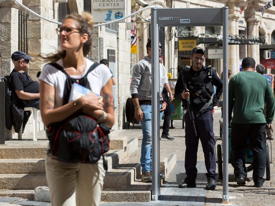 An Israeli police officer stands at a metal detector