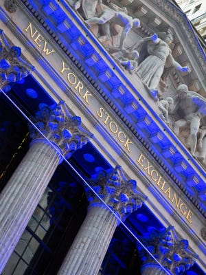 Colorful holiday lights are beamed onto the New York Stock Exchange, Thursday, Dec. 3, 2015, in New York. (AP Photo/Bebeto Matthews)