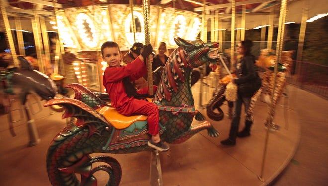 Logan Johnson, 5, of Scottsdale, rides the Phoenix Zoo's carousel in his Halloween costume.