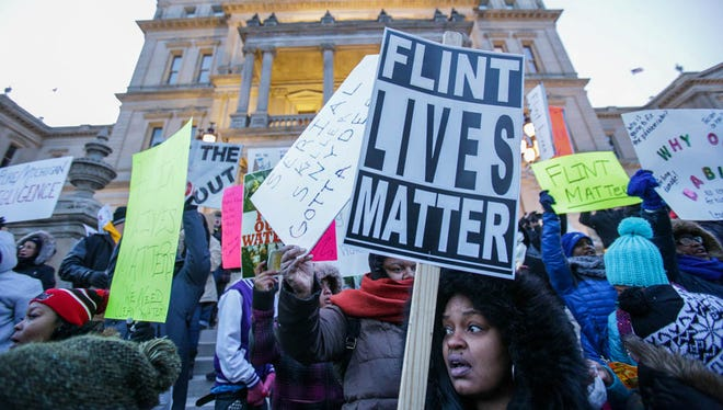 Shakya Pea, 33, of Flint holds ups a sign, Flint Lives Matter.