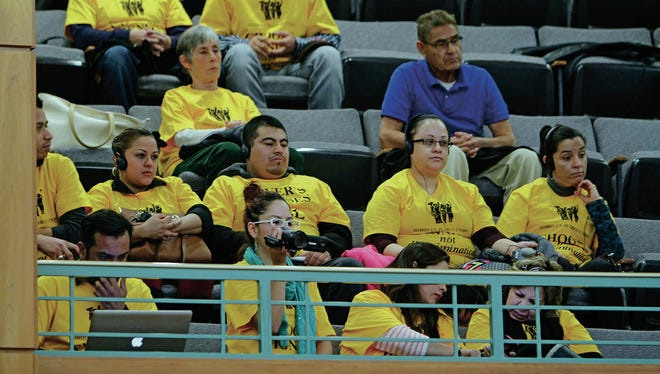 "Members of the Somos Un Pueblo Unido group wearing ""Choose Dignity not Discrimination"" T-shirts sit in attendance at the Roundhouse in Santa Fe."