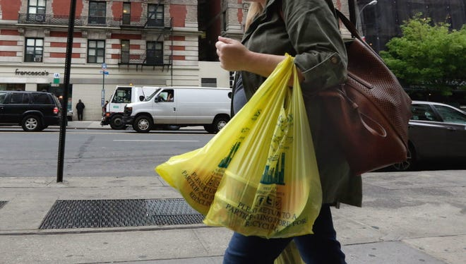A woman carries her purchase in plastic bags from a supermarket on New York's Upper West Side. Merchants in New York who now hand out billions of free plastic bags each year would have to start charging 5 cents each under a law that was to have gone into effect Wednesday in the city.