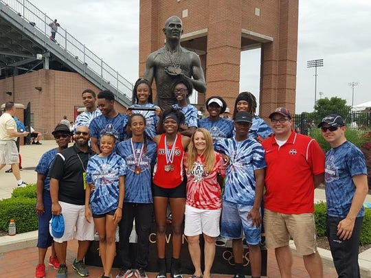 Jolinda Miller and Hughes High School staff share a moment with Tiona Lattimore at the OHSAA state track meet when she was in high school.