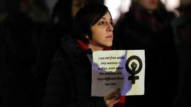 A women holds up a sign with a quote from the writer Audre Lorde during an International Women's Day rally in Seattle, Washington on March 8, 2017.