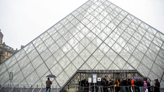 Tourists stand outside the Louvre museum, in Paris, France on Sunday. The spreading coronavirus epidemic shut down France's Louvre Museum on Sunday, with workers who guard its trove of artworks fearful of being contaminated by the museum's flow of visitors from around the world.