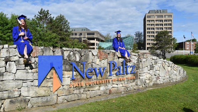 From left, Jennifer Ferrantelli of Highland Mills, and Alyssa Gentile of Rockland County sit on top of the New Paltz sign at the entrance to SUNY New Paltz prior to commencement May 15.