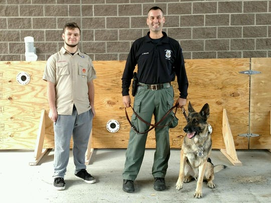Evan Trabold, 17, of Boy Scout Troop 195 with Greece Police Officer Jeff Phillips and Greece Police Department K9 officer Chip in front of the scent wall Evan constructed for his Eagle Scout project.