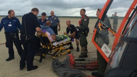 An MH-65 Dolphin helicopter crew from Air Station Atlantic City, N.J., transfers a man to local emergency medical services personnel, at the air station, July 15, 2014. The aircrew medevaced the man from a fishing boat about 45 miles off shore from Ocean City after the man experienced health issues.