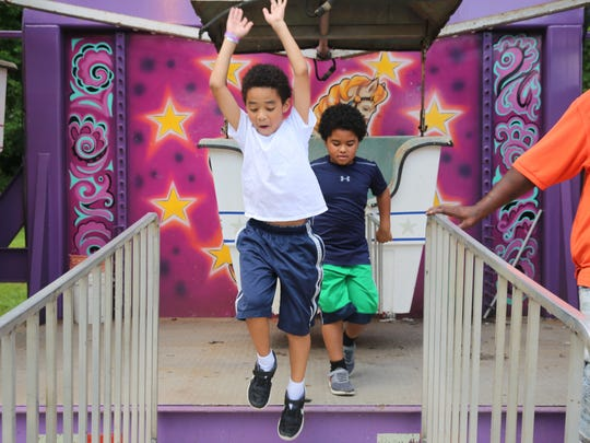 Ethan Fury, 7, leaps after his ride on the Ferris wheel