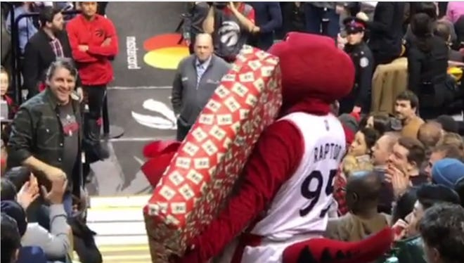 The Toronto Raptors mascot dropped a flatscreen television won by a fan.