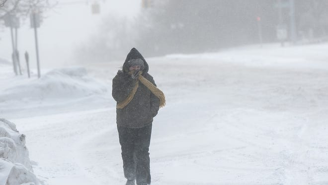 Naomi Henderson, of Lansing, braces herself against the bitter snow and wind. Bitter cold temperatures will push into the Lansing area Sunday, with temperatures possibly dropping to zero Sunday night.
