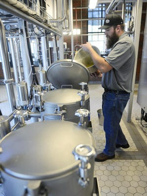 Third Street Brewhouse head brewer Karl Schmitz adds hops to the hops doser while making beer in Cold Spring.