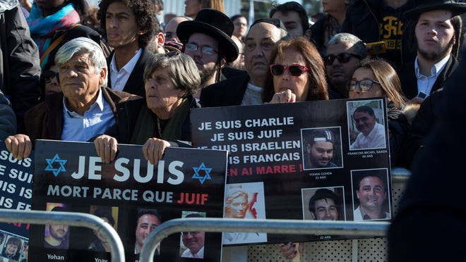 French Israelis hold placards during funeral services Tuesday for French Jewish victims of an attack on a kosher grocery store in Paris last week.