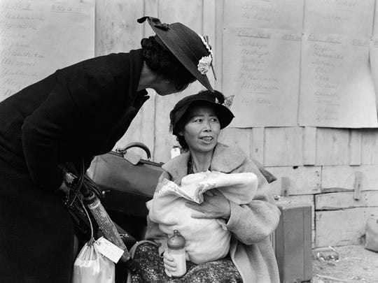 """A mother and child in Centerville, California, await an """"evacuation"""" bus on May 9, 1942. The notices on the wall behind them list the names of families and their assigned buses and departure times. This photo is featured in an exhibit on Japanese internment at the FDR Presidential Library and Museum in Hyde Park."""