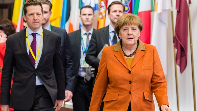 German Chancellor Angela Merkel, right, arrives for an EU summit in Brussels on Monday, March 7, 2016.