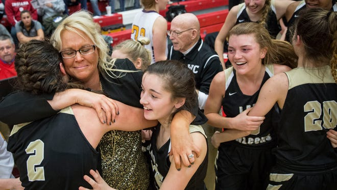 Winchester players celebrate a win against Paoli for the 2A Semi-State Championsihp on Feb. 17 at Jeffersonville High School. Winchester won with a final score of 49-47 in overtime.