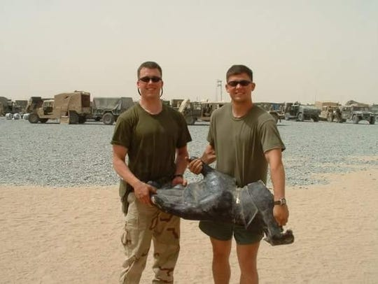 Marine Lt. Alexander Edmund Wetherbee and Lt. Tom Vanderhorst with the hand removed from the Saddam Hussein statue pulled down in Firdos Square in 2003.
