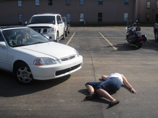 We asked folks to tells us about (and show us) their first cars. Megan Wyatt of Lafayette sent this funny picture of her first car, a 1998 two-door Honda Civic, and a friend joking by lying in front of the car.