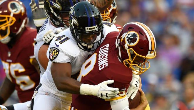 Baltimore Ravens cornerback Anthony Levine, left, sacks Washington Redskins quarterback Kirk Cousins in the first half of a preseason NFL football game, Thursday, Aug. 10, 2017, in Baltimore. The Ravens would win the game, 23-3. (AP Photo/Gail Burton)